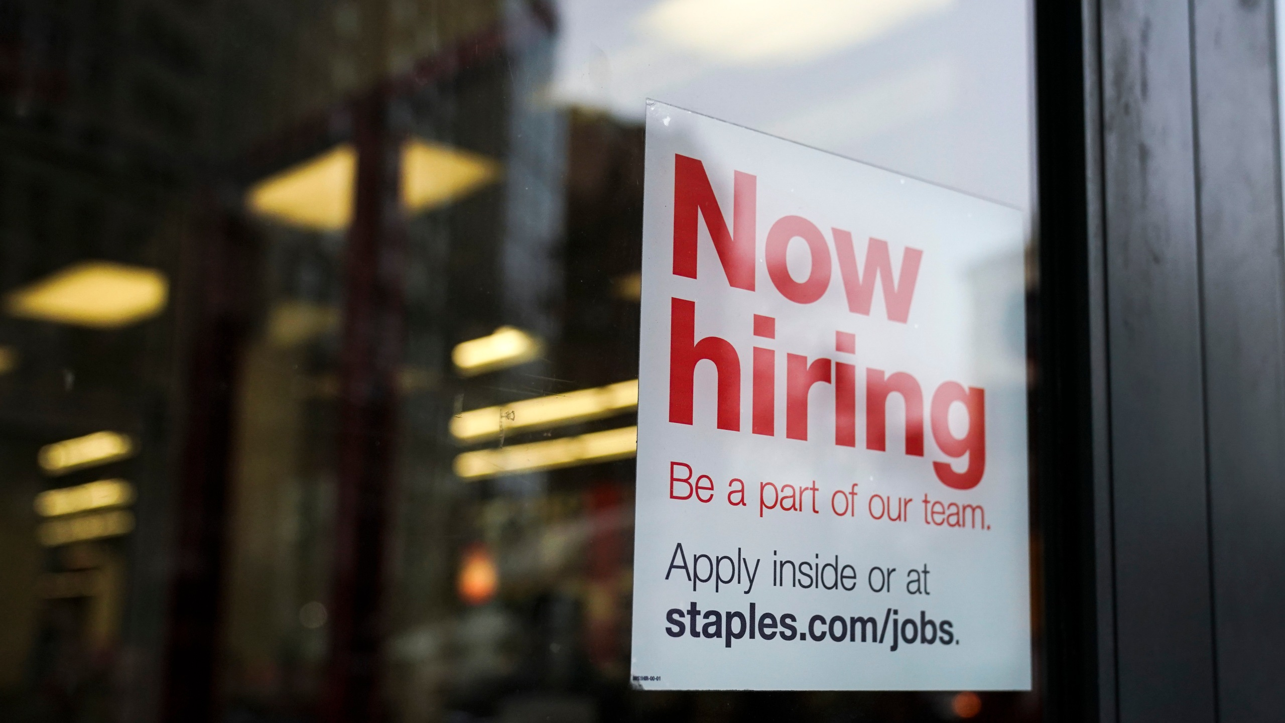 Picture of a 'now hiring' sign hangs on the door of a Staples store