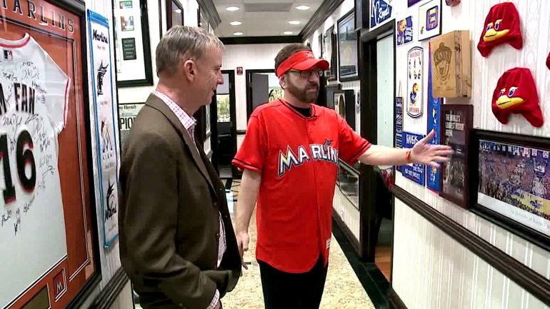 "Laurence Leavy, also known as ""Marlins Man,"" shows off some sports memorabilia commemorating his trip Allen Fieldhouse in Lawrence, Kansas."