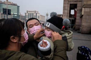 Picture of parents putting a sick mask over a child