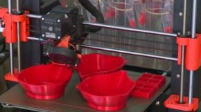 Picture of red plastic masks being 3D printed
