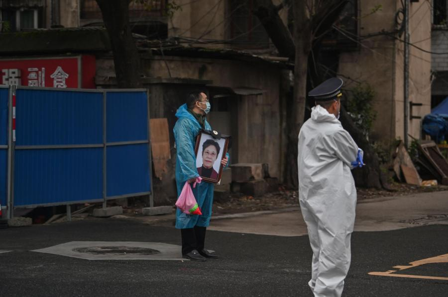 Chinese man holds portrait of dead wife