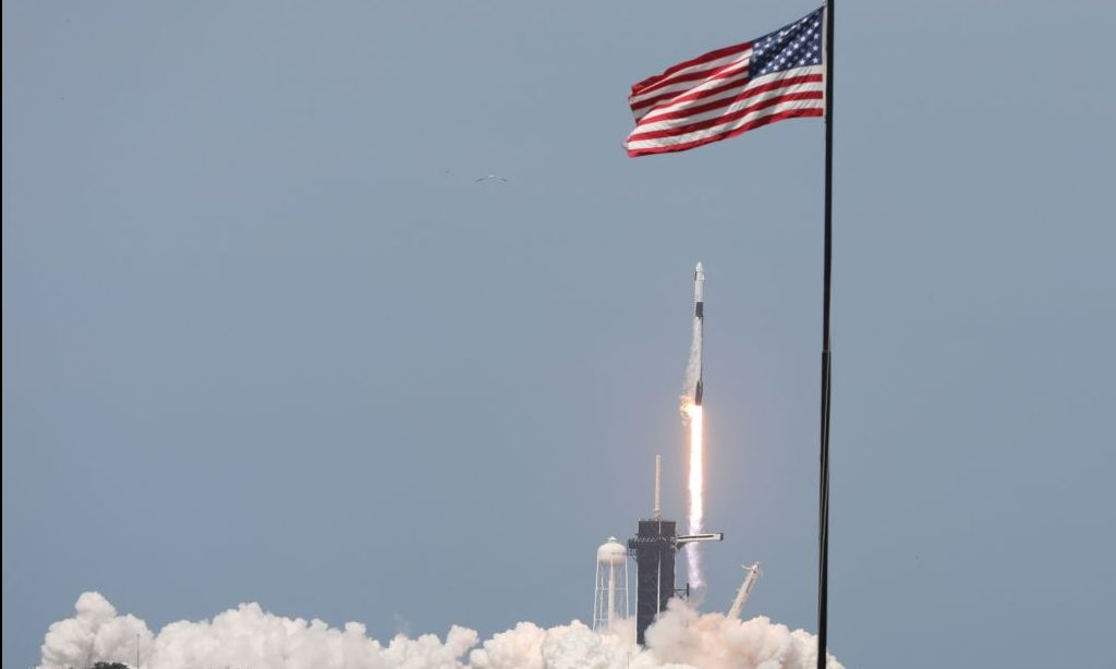 Picture of rocket launching behind American flag