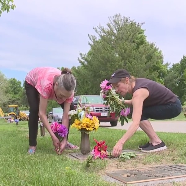 Picture of women laying flowers on grave site