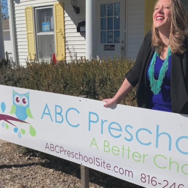 Picture of woman standing behind new preschool sign
