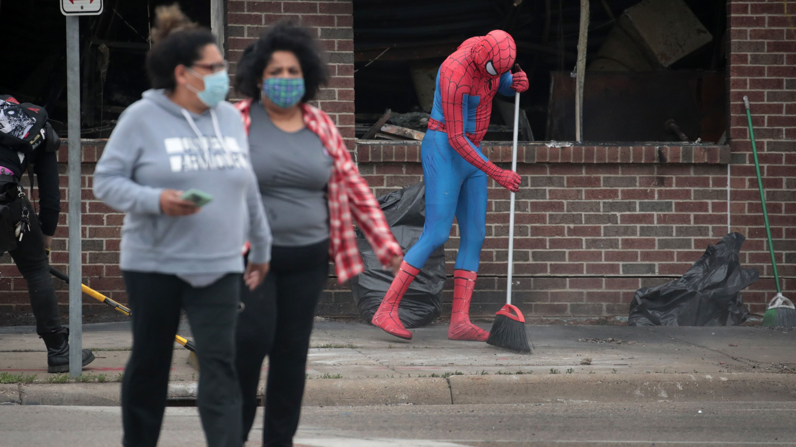 A person dressed as Spiderman sweeps the sidewalk picture