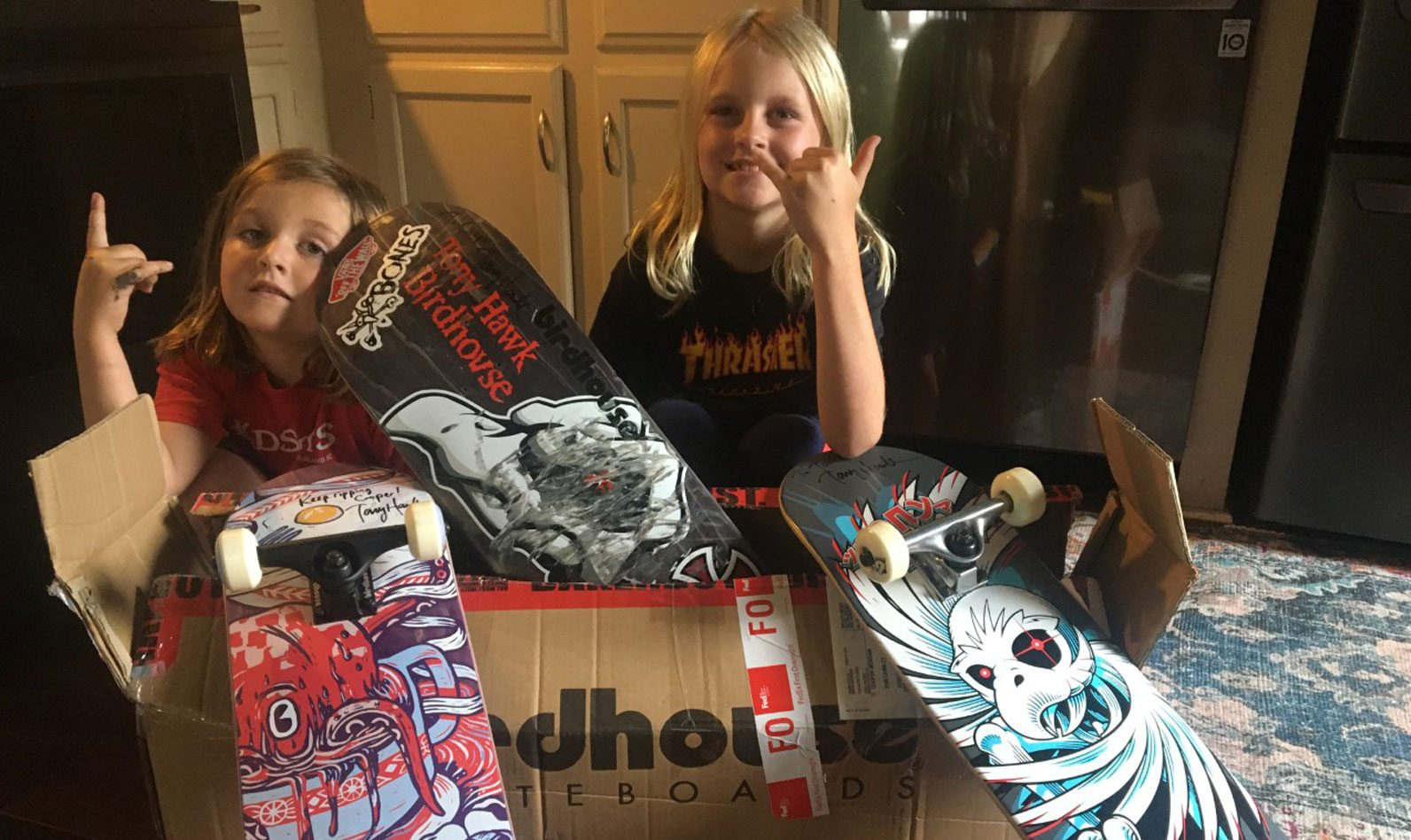 Picture of two kids with Tony Hawk's skateboards
