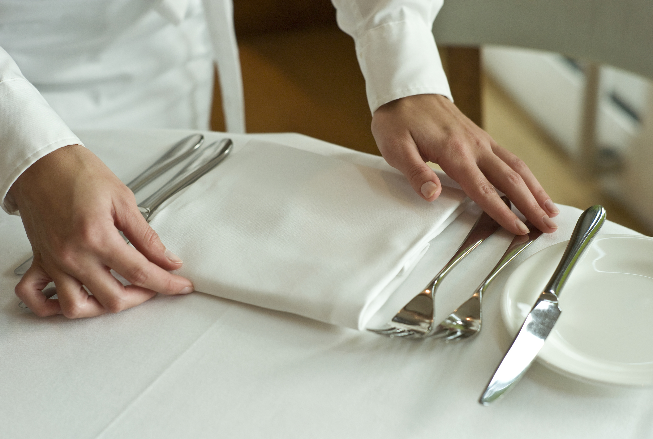 Picture of Waitress adjusting table settings in restaurant, mid section