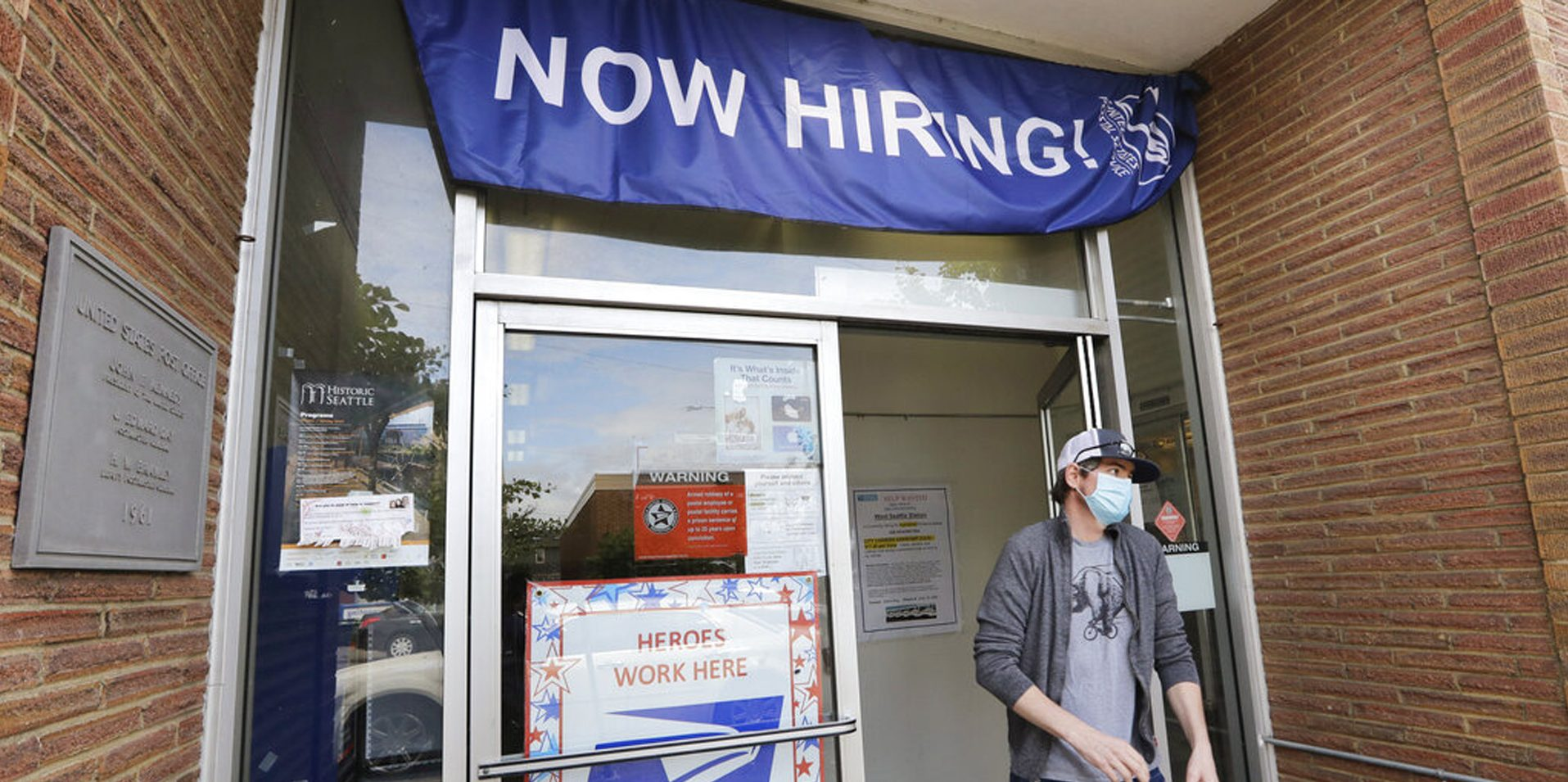 Picture of man with mask near hiring sign