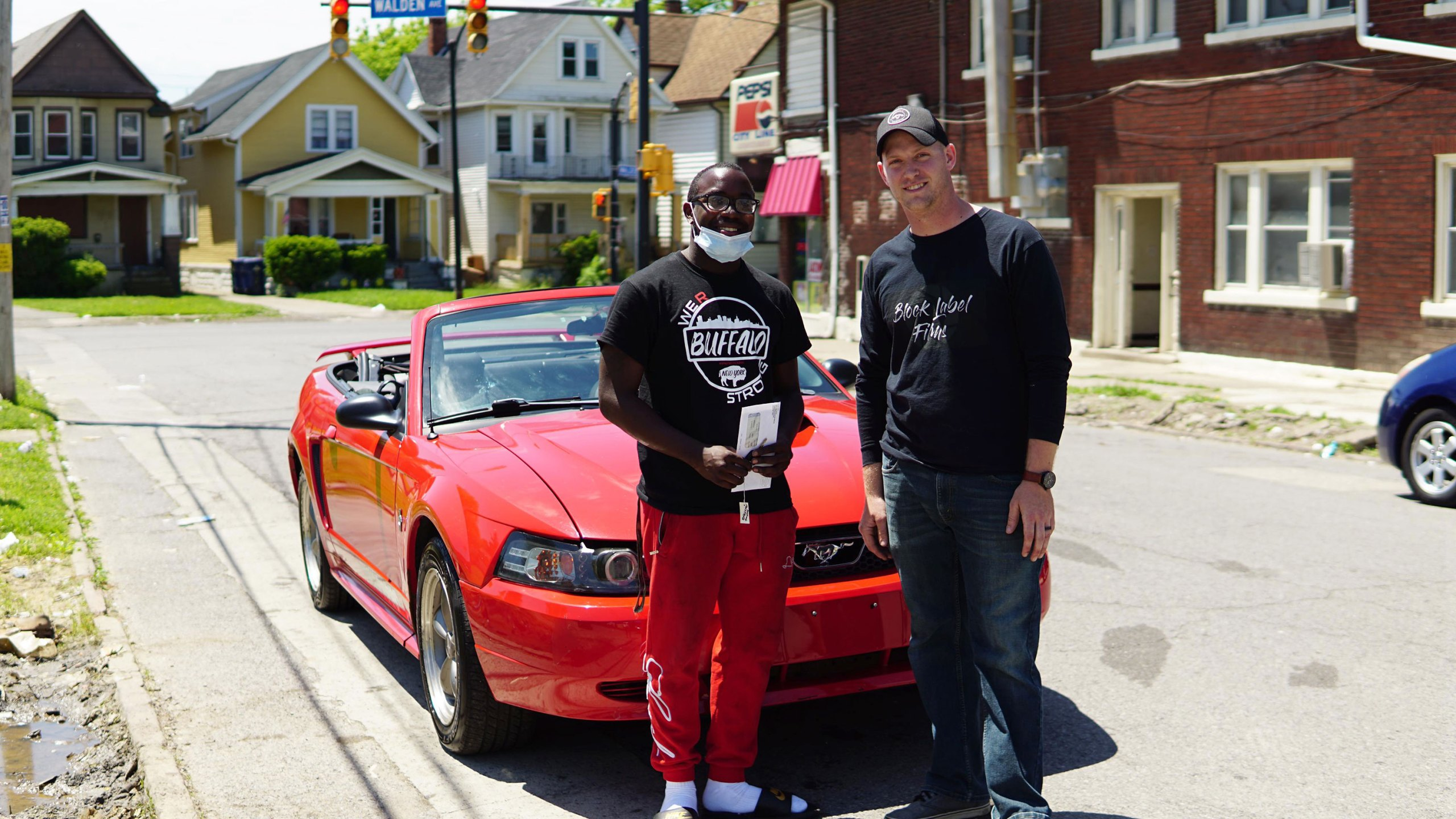 Picture of man and teen standing in front of red Mustang
