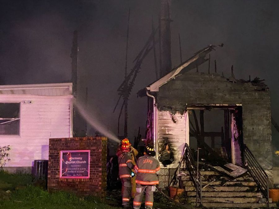 Picture of firefighter spraying water on destroyed church