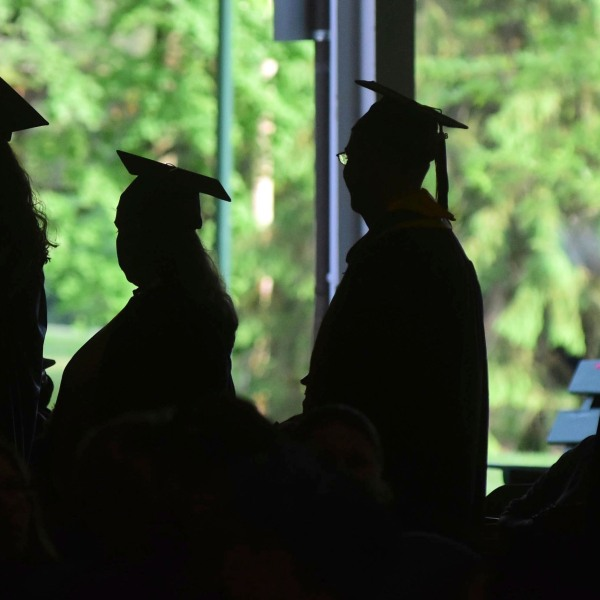 Silhouettes of students graduating