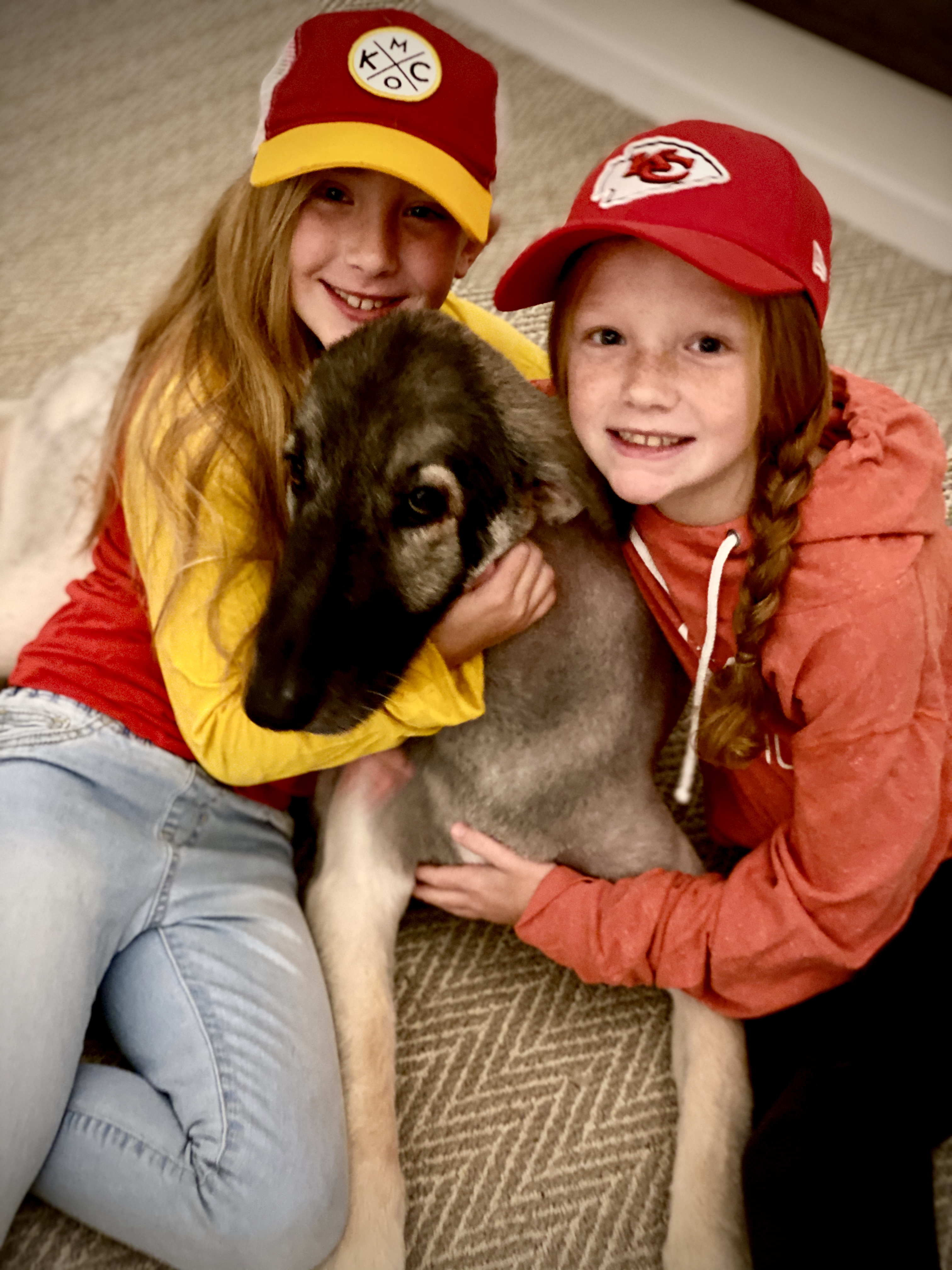 Picture of girls snuggling with dog wearing Chiefs gear