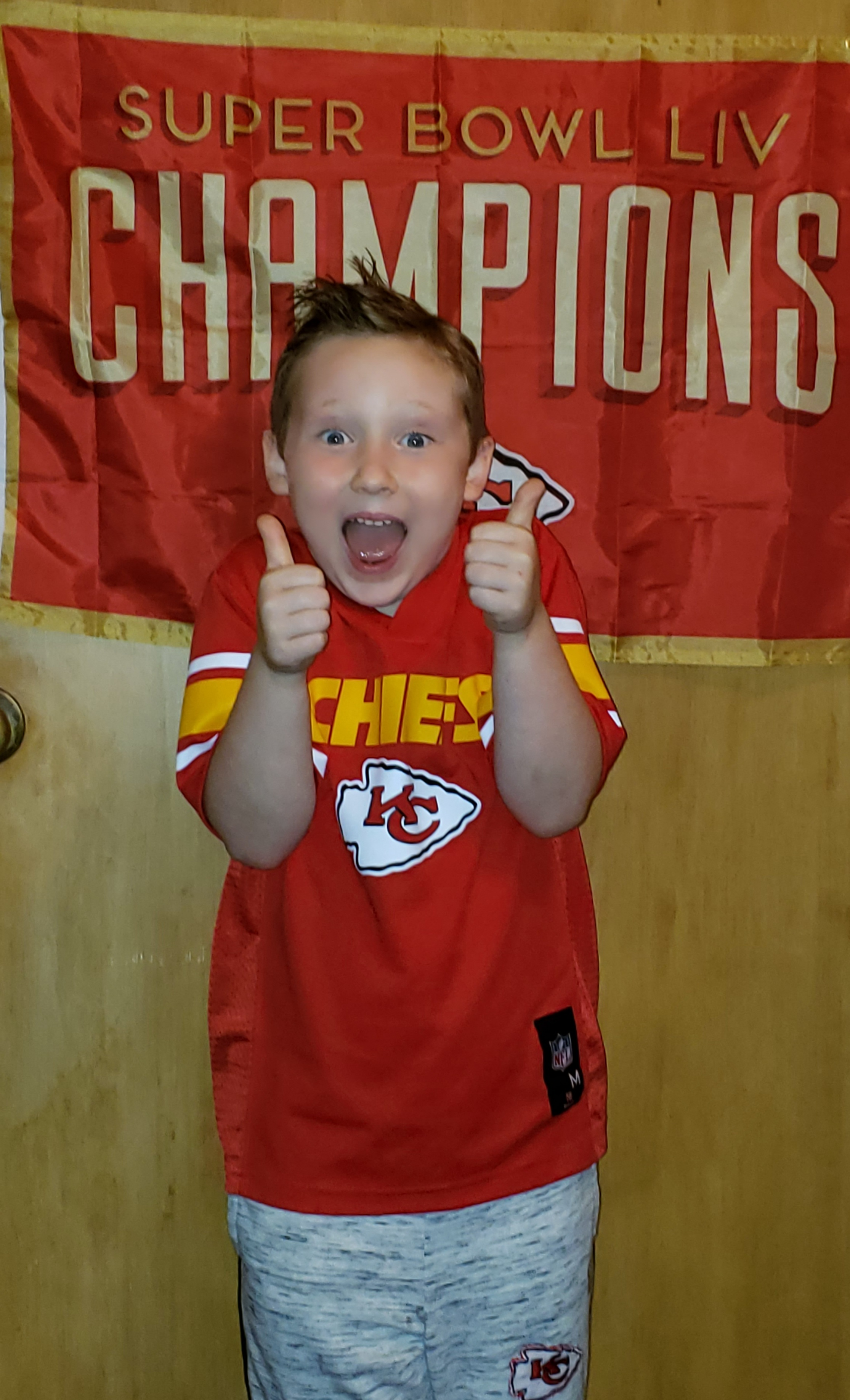 Picture of kid giving thumbs up wearing Chiefs shirt