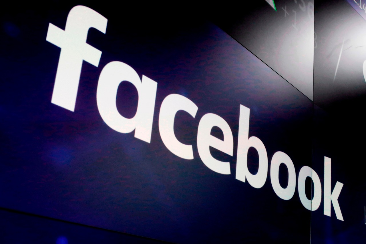 FILE – In this March 29, 2018, file photo, the logo for Facebook appears on screens at the Nasdaq MarketSite in New York's Times Square.  Academic