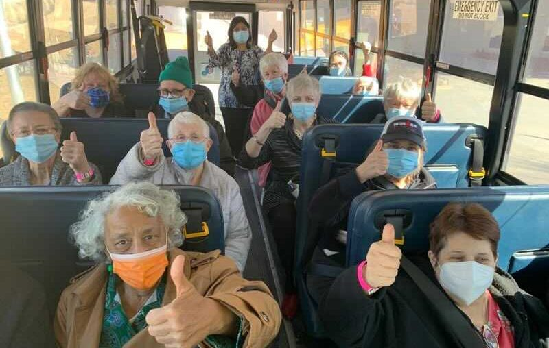 Picture of seniors on a NKC bus with thumbs up