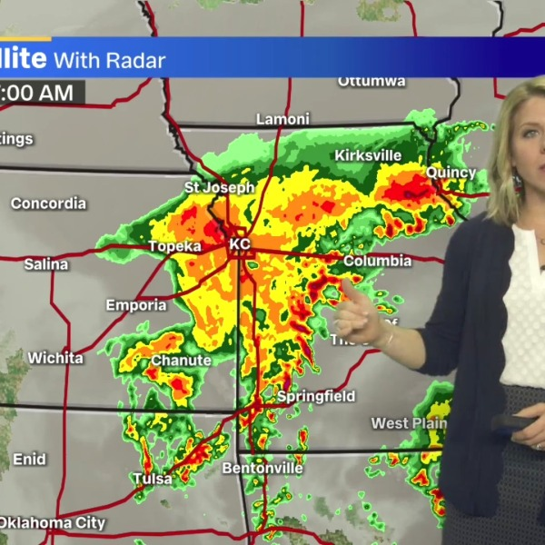 Picture of Karli pointing to rain on map