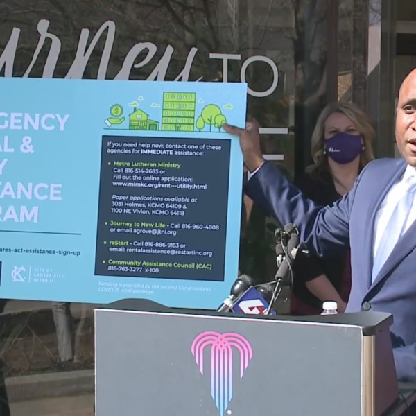 Picture of Mayor Lucas holding rent assistance sign