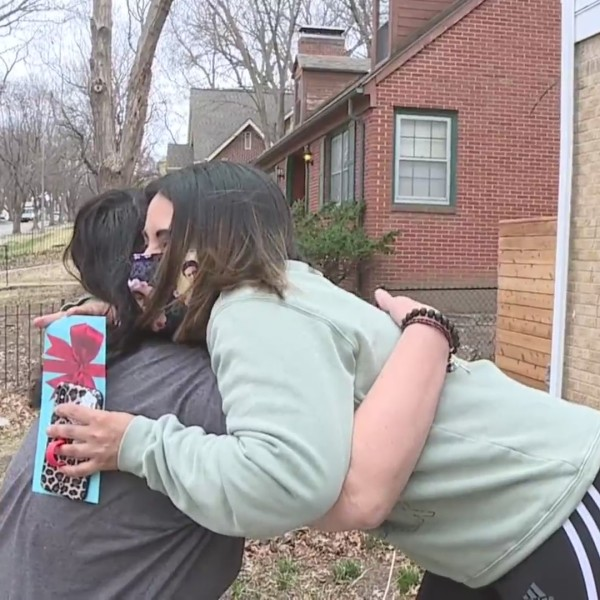 Picture of women hugging with gift card in hand