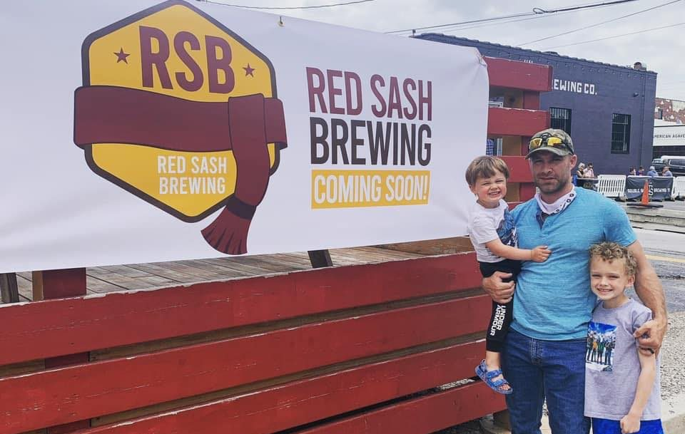 Picture of Pat Mitchell next to Red Sash Brewing sign