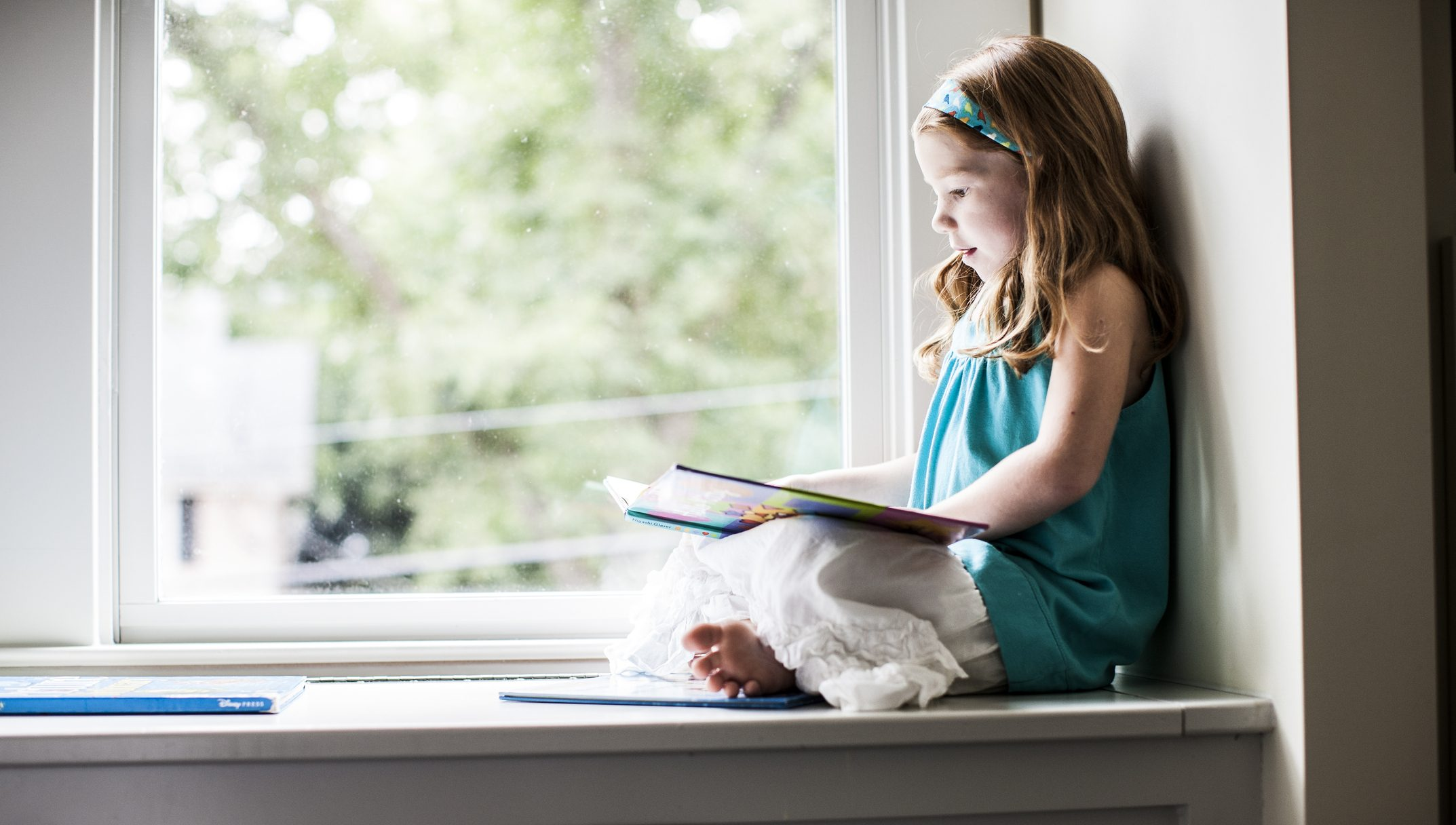 Girl (6yrs) sitting in window reading a book