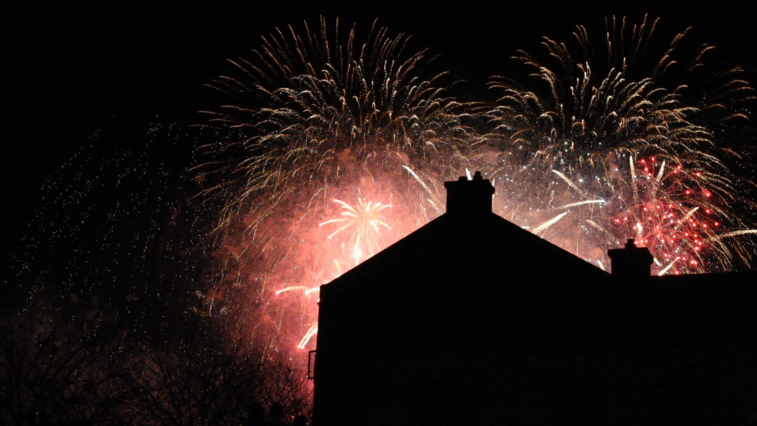 Picture of fireworks with houses in the foreground as silhouette